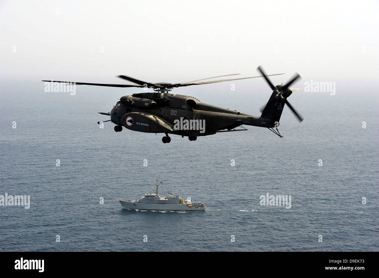 A CH-53 Sea Stallion flies above the mine countermeasures ship USS Ardent - Stock Image
