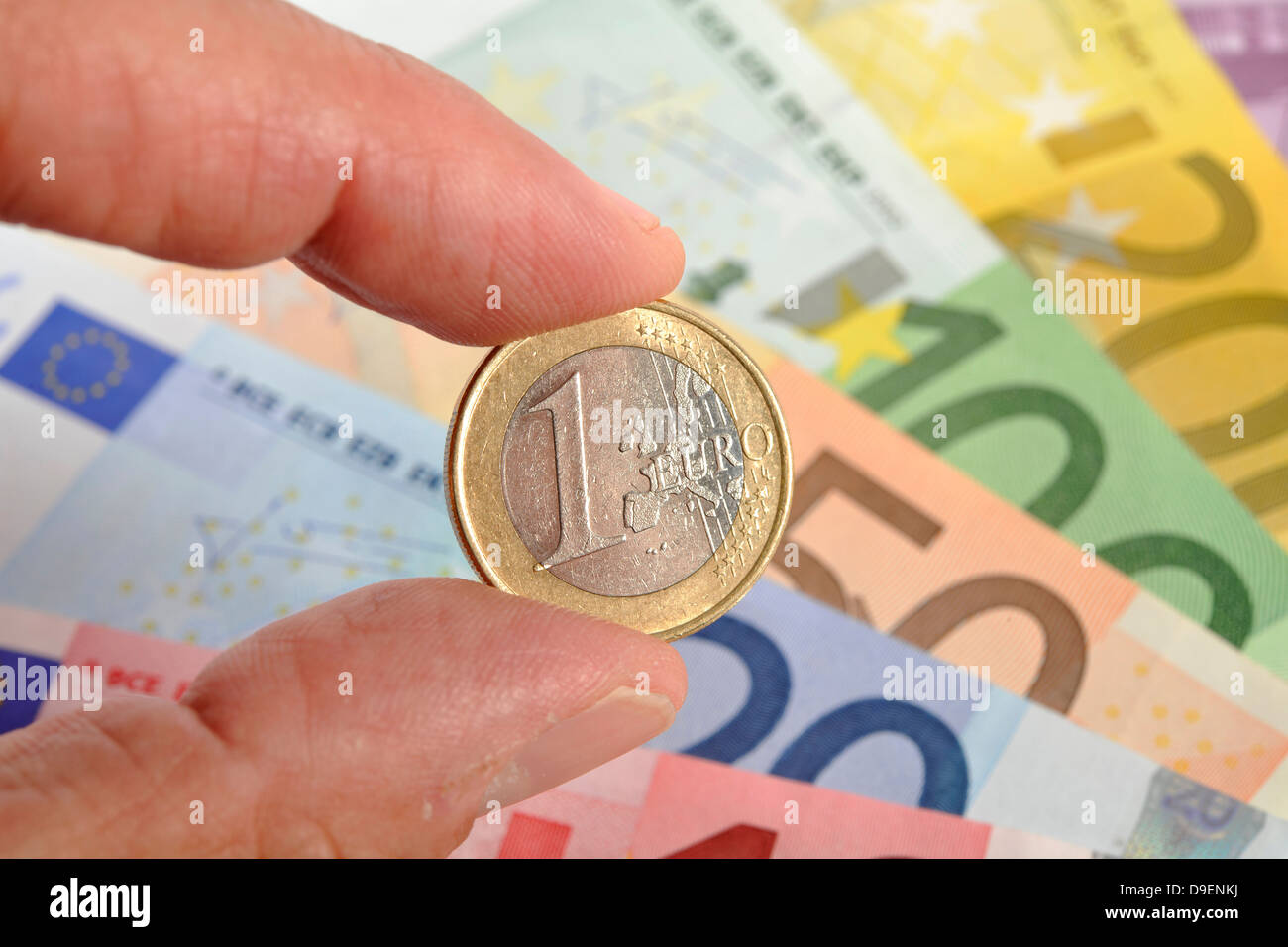 various euro-bank notes, bank notes, coins, fields, 1-euro-coin between fingers - Stock Image