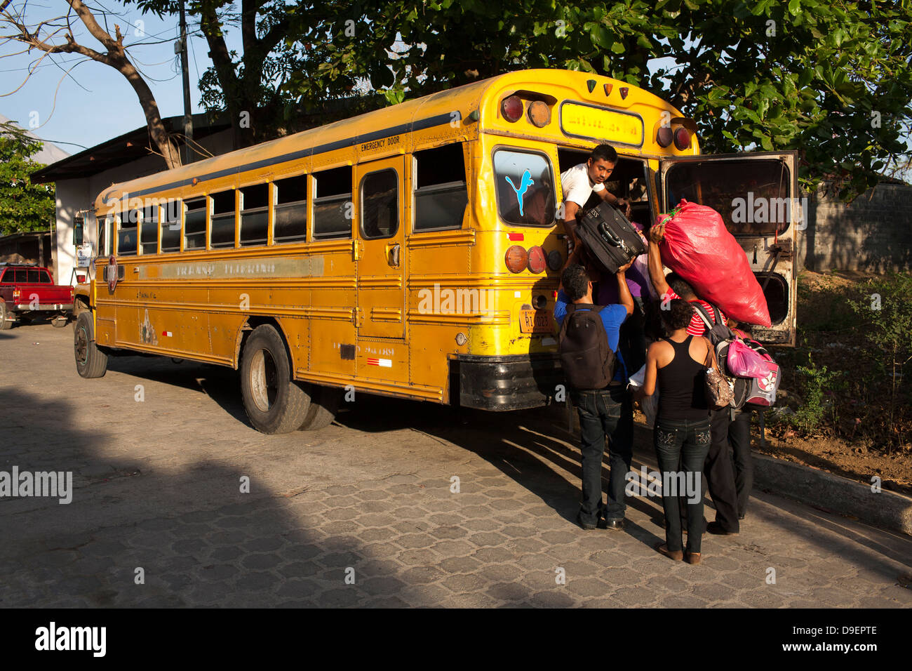 Nicaraguans load bags and luggage into the bus in Moyogalpa on Ometepe in the middle of Lake Nicaragua Stock Photo