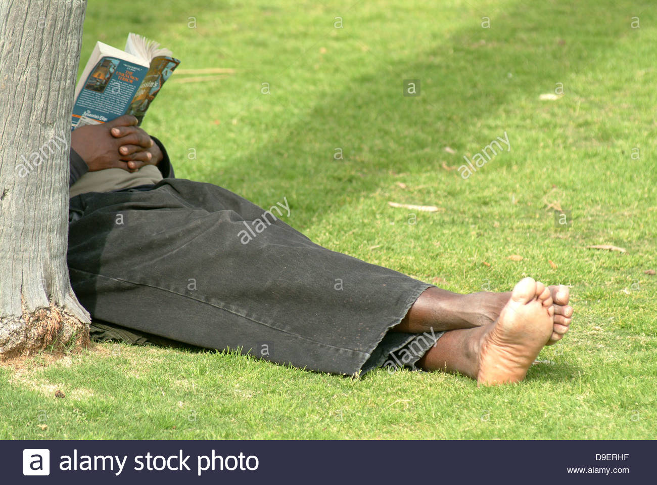 african america barefoot black book economy employment grass hobo homeless jobless lying park poor poverty reading - Stock Image