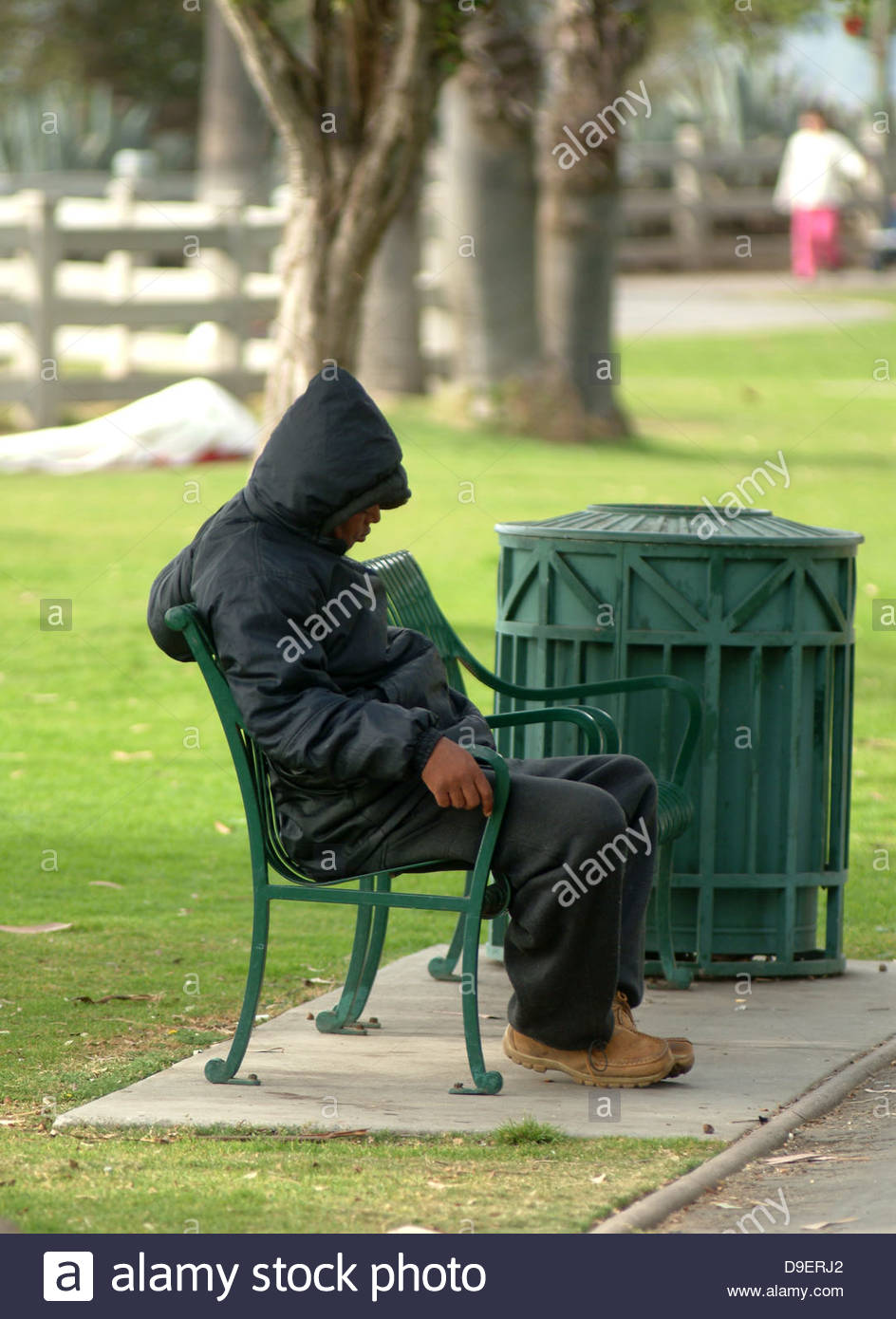 adult america grass hobo homeless jobless male man one park poor poverty sat seated shelter side view single sitting - Stock Image