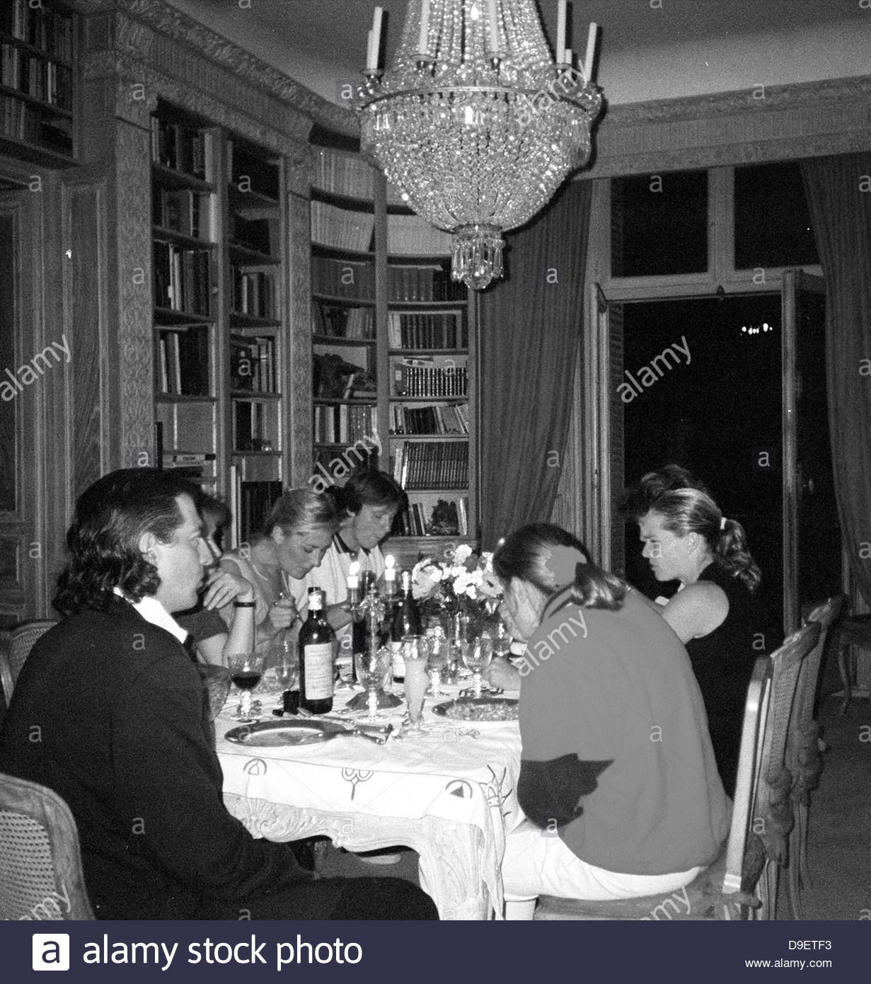 black and white chandelier dinner drinks eating eats family formal glasses hunger hungry indoors inside luxurious - Stock Image