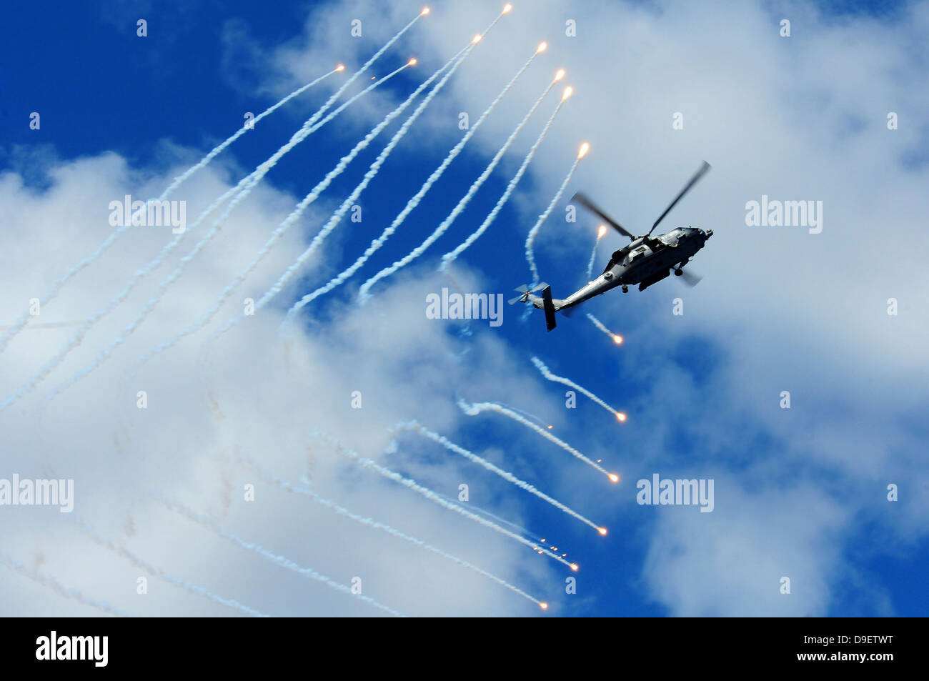 An HH-60H Sea Hawk helicopter releases countermeasure flares. Stock Photo