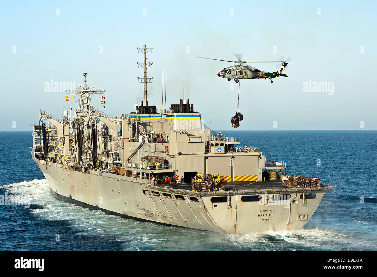 An MH-60S Knighthawk lifts cargo from the fast combat support ship USNS Rainier. - Stock Image