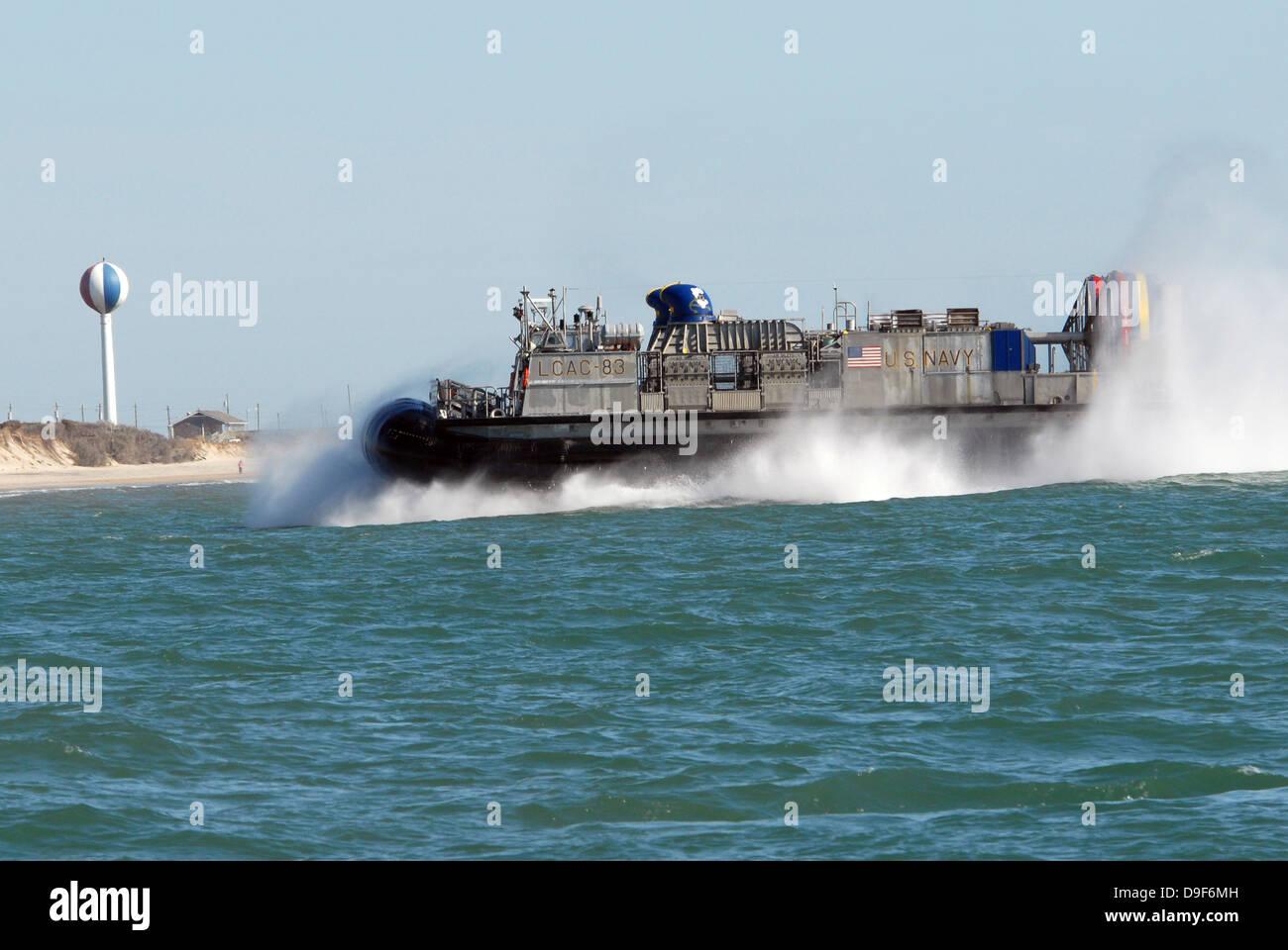 A landing craft air cushion prepares to land on the beach. Stock Photo