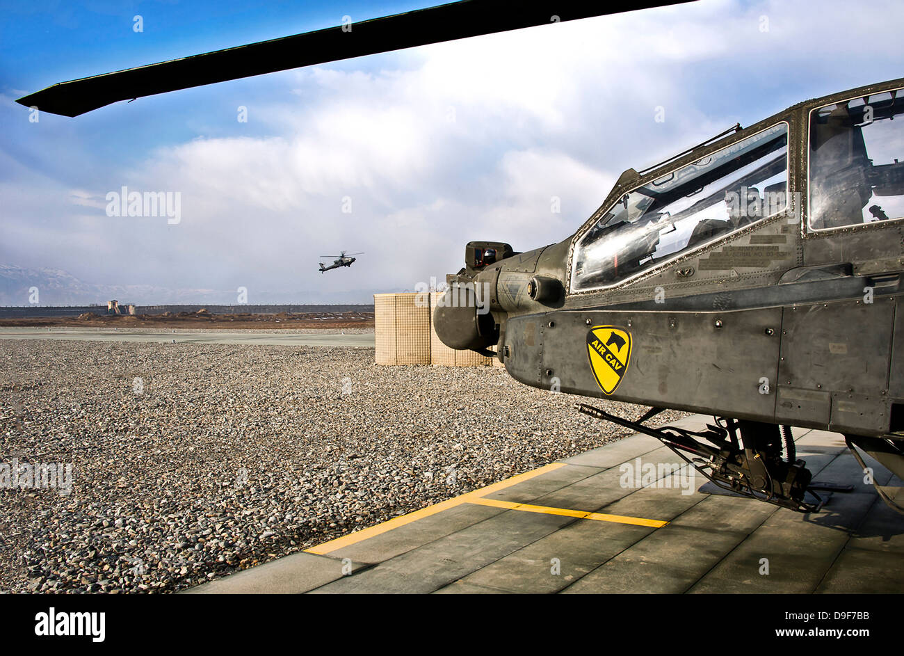 An AH-64D Apache helicopter comes in for a landing at a military base in Afghanistan. - Stock Image
