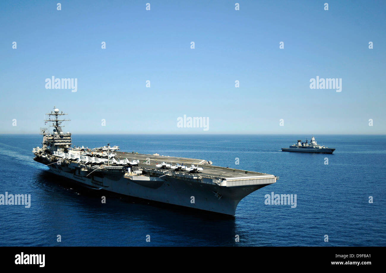 USS Harry S. Truman cruises alongside the German Navy frigate FGS Hessen. - Stock Image