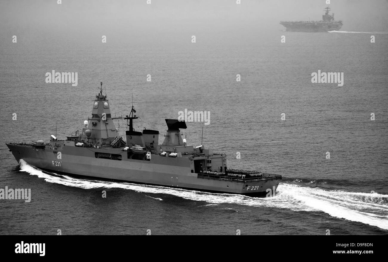 German navy frigate FGS Hessen cruises alongside USS Harry S. Truman. - Stock Image