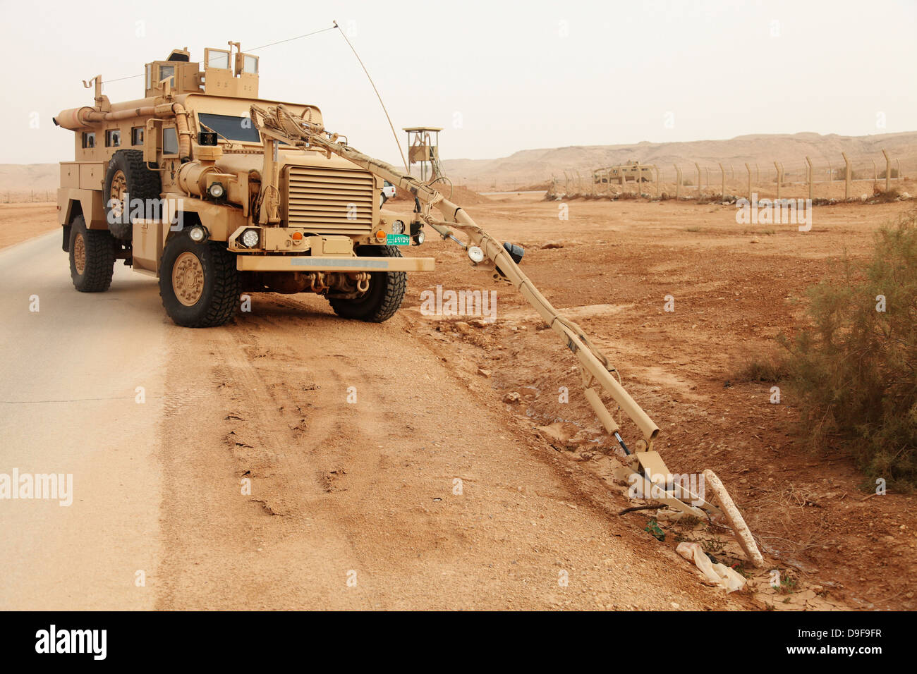 A MRAP vehicle disassembles an improvised explosive device. - Stock Image