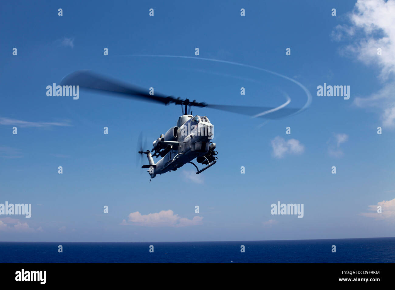 An AH-1 Cobra in flight over the Philippine Sea. - Stock Image