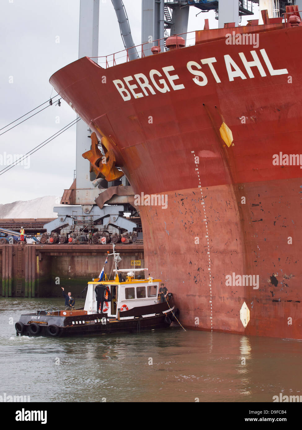 Men on their small boat preparing work on the Berge Stahl one of the largest bulk carriers in the world. Port of - Stock Image