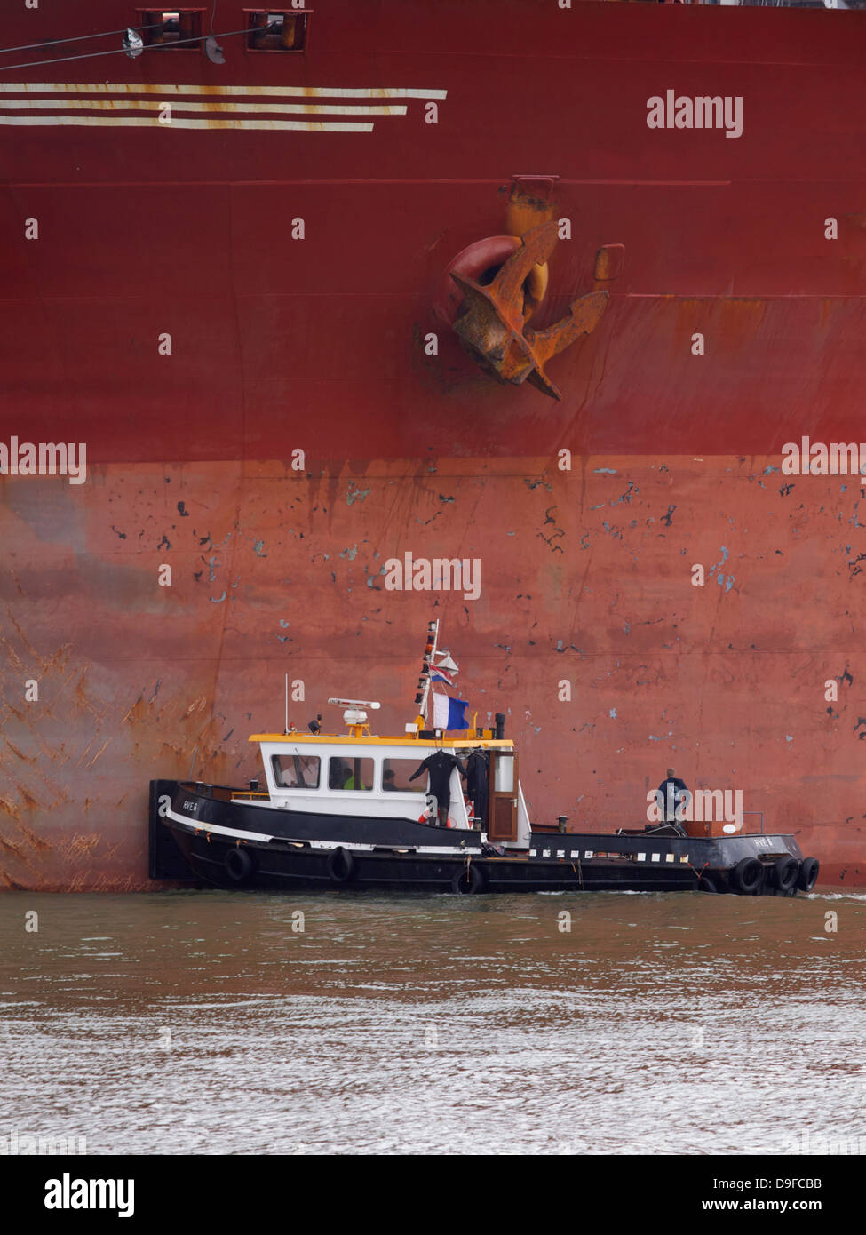 Small boat next to an anchor of the Berge Stahl, one of the largest bulkcarriers in the world. Port of Rotterdam - Stock Image