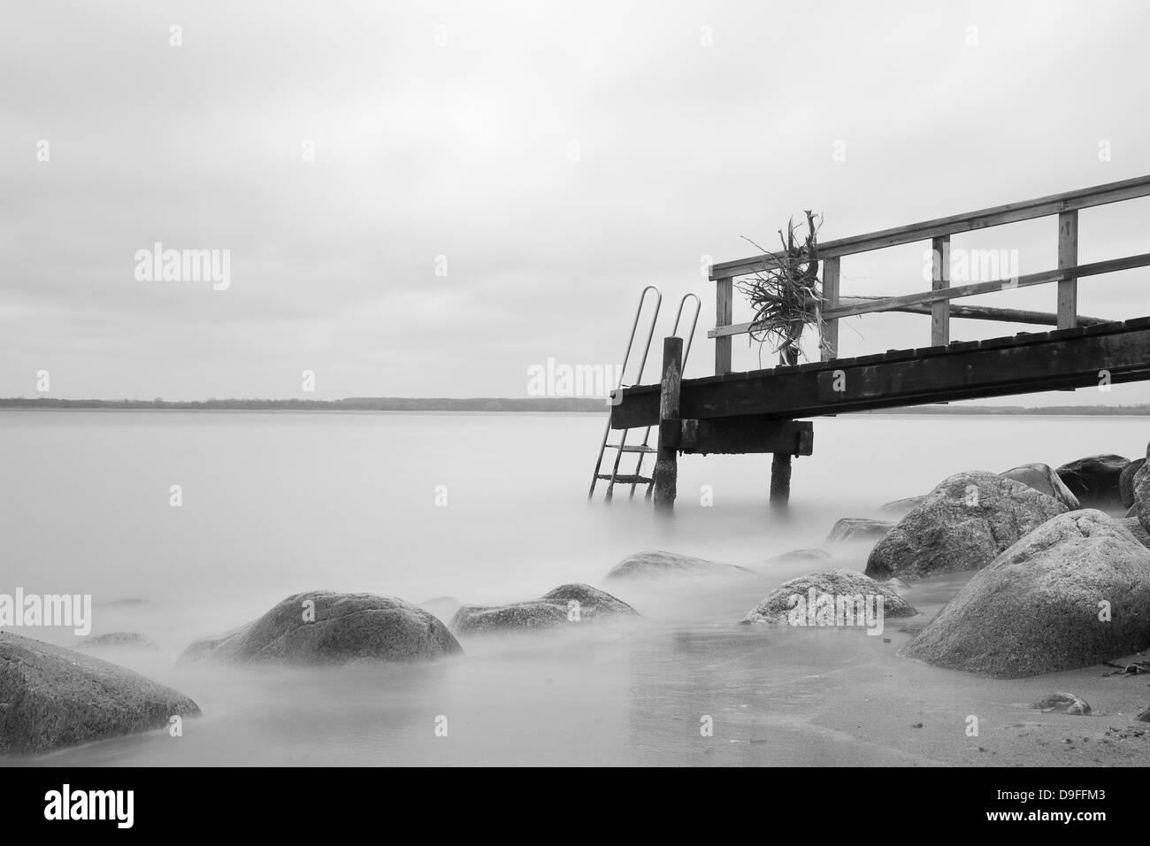 Holzsteg mit einer Leiter an der Ostsee  Wooden pier with a ladder on the Baltic Sea  - Stock Image