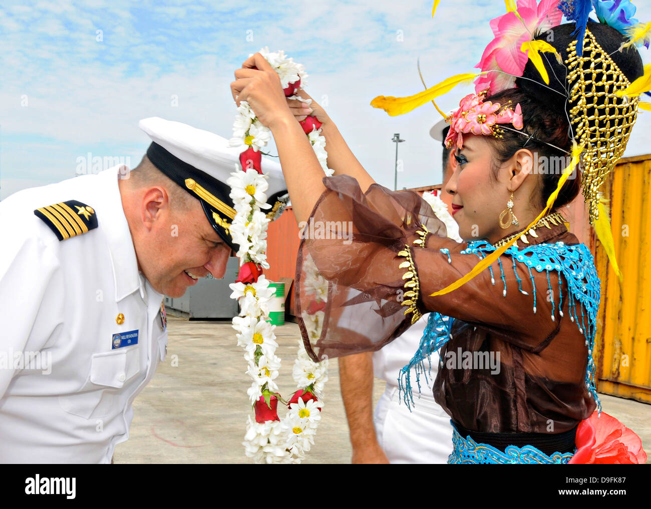 US Navy Capt. Will Pennington, commanding officer of the 7th Fleet flagship USS Blue Ridge is welcomed with a traditional - Stock Image