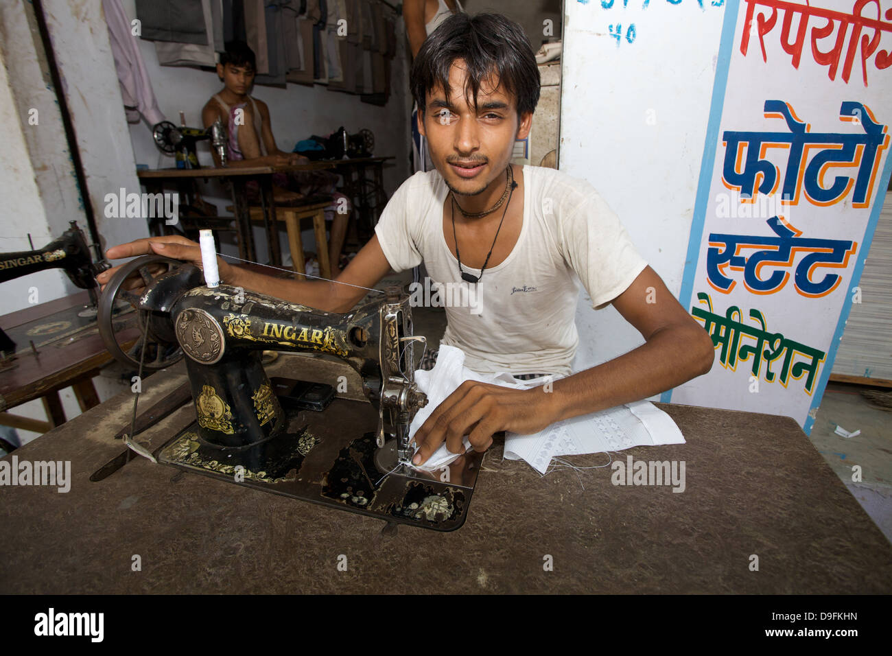 A young male working a sewing machine in Delhi In India. Indian business. Indian clothing business. Indian tailor. - Stock Image