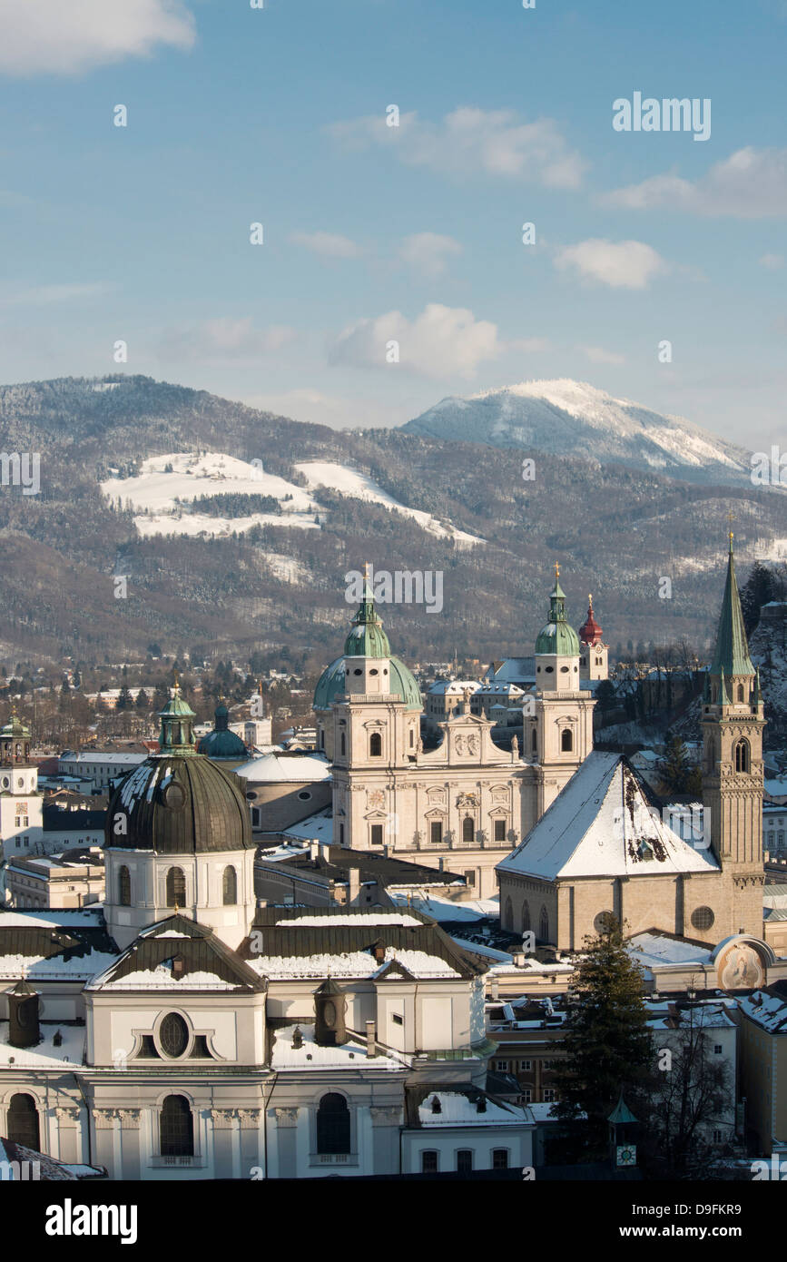 The domes of the Salzburg Cathedral and Franziskaner Kirche in the Altstadt and snow covered mountains, Salzburg, - Stock Image