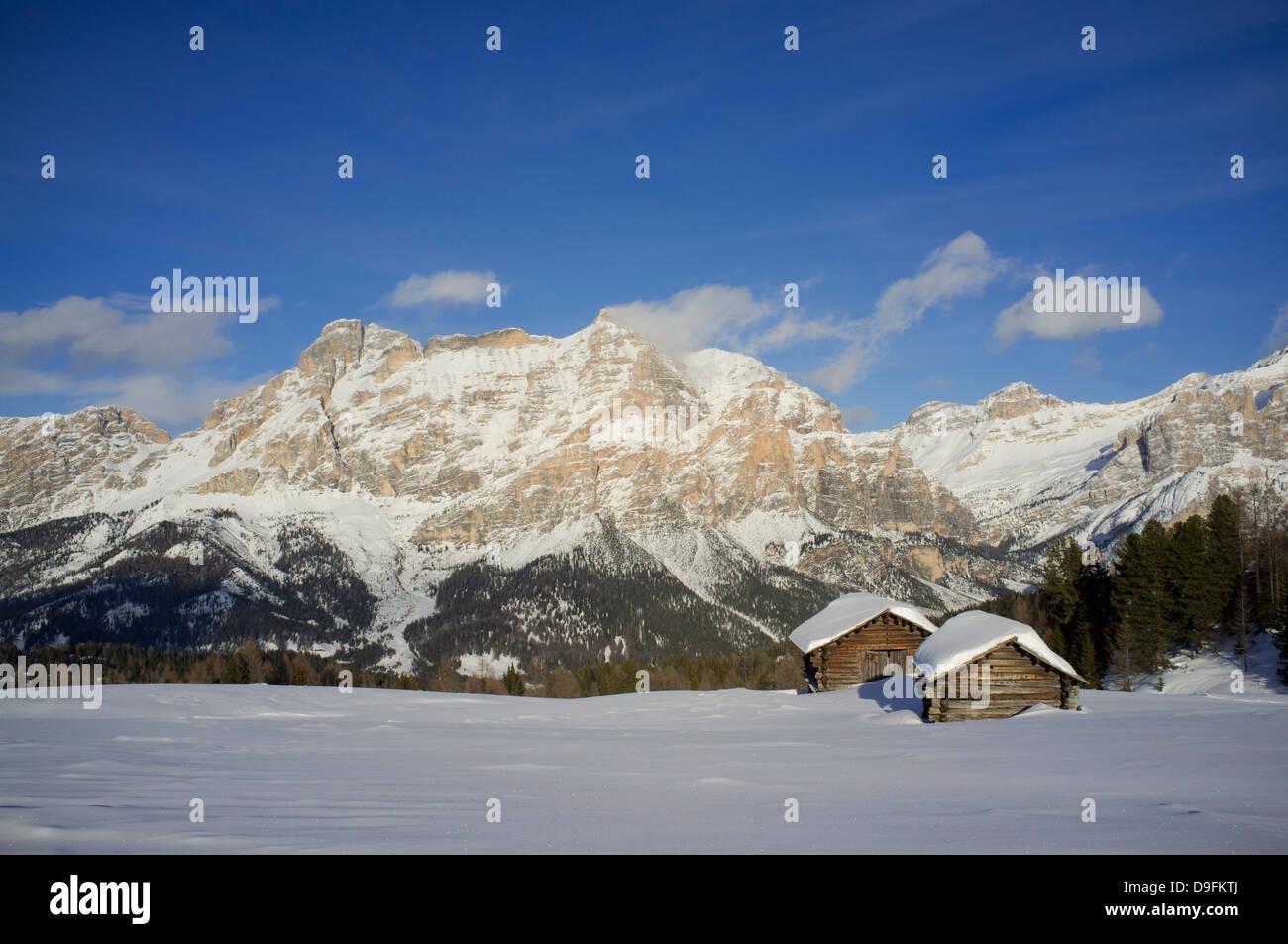 Mounts Lavarella and Conturines behind a pair of barns at the Alta Badia ski resort near Corvara, Dolomites, South - Stock Image