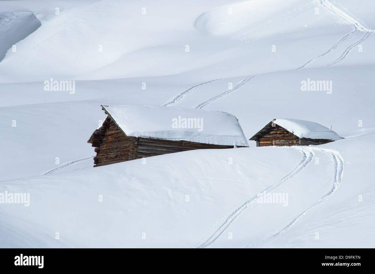 Two old wooden barns surrounded by deep snow and ski tracks in the Dolomites, South Tyrol, Italy - Stock Image