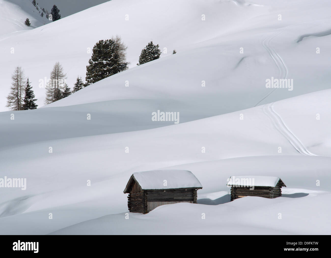Two old wooden barns surrounded by deep snow in the Dolomites, South Tyrol, Italy - Stock Image