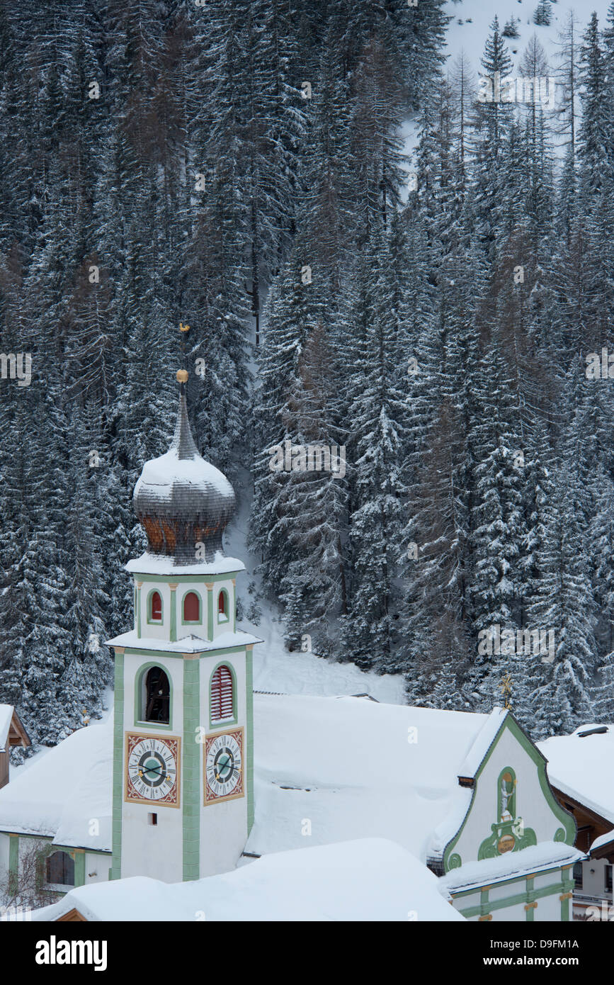 The Church of San Cassiano and snow covered trees behind, San Cassiano, Dolomites, South Tyrol, Italy - Stock Image