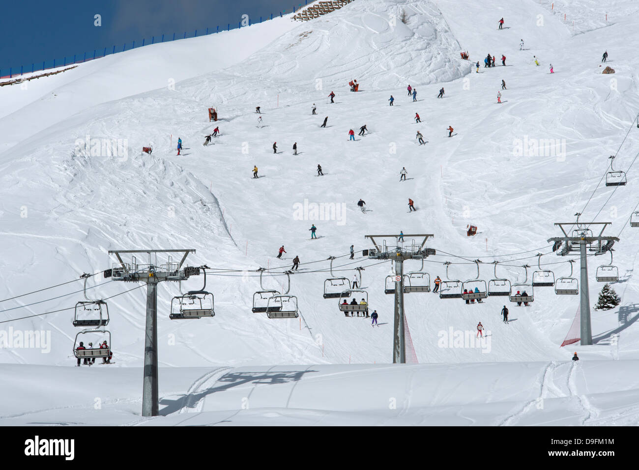 A chairlift and skiers on piste at Passo Sella in the Dolomite Mountains, South Tyrol, Italy - Stock Image
