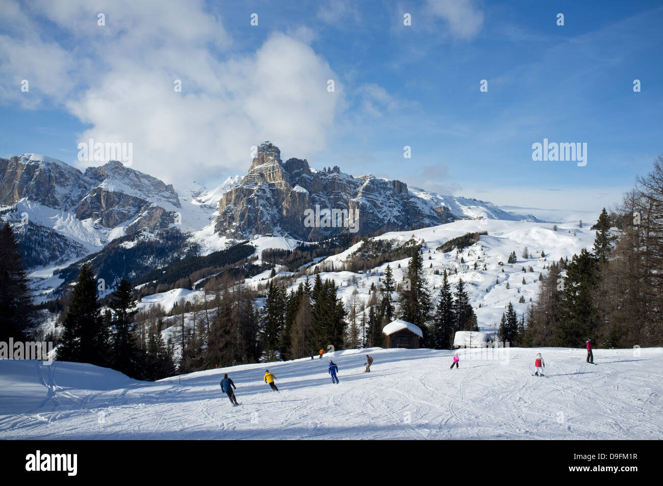 Skiers at the Alta Badia ski resort with Sassongher Mountain in the distance, Dolomites, South Tyrol, Italy - Stock Image