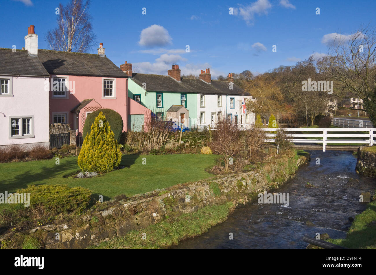 Pastel coloured cottages alongside the beck in Calthwaite, John Peel Country, Cumbria, England, UK - Stock Image
