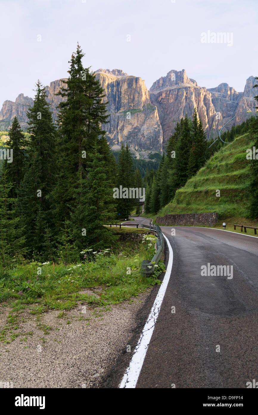 Mountain road and the Sassolungo mountains in the Dolomites near Canazei, Trentino-Alto Adige, Italy - Stock Image