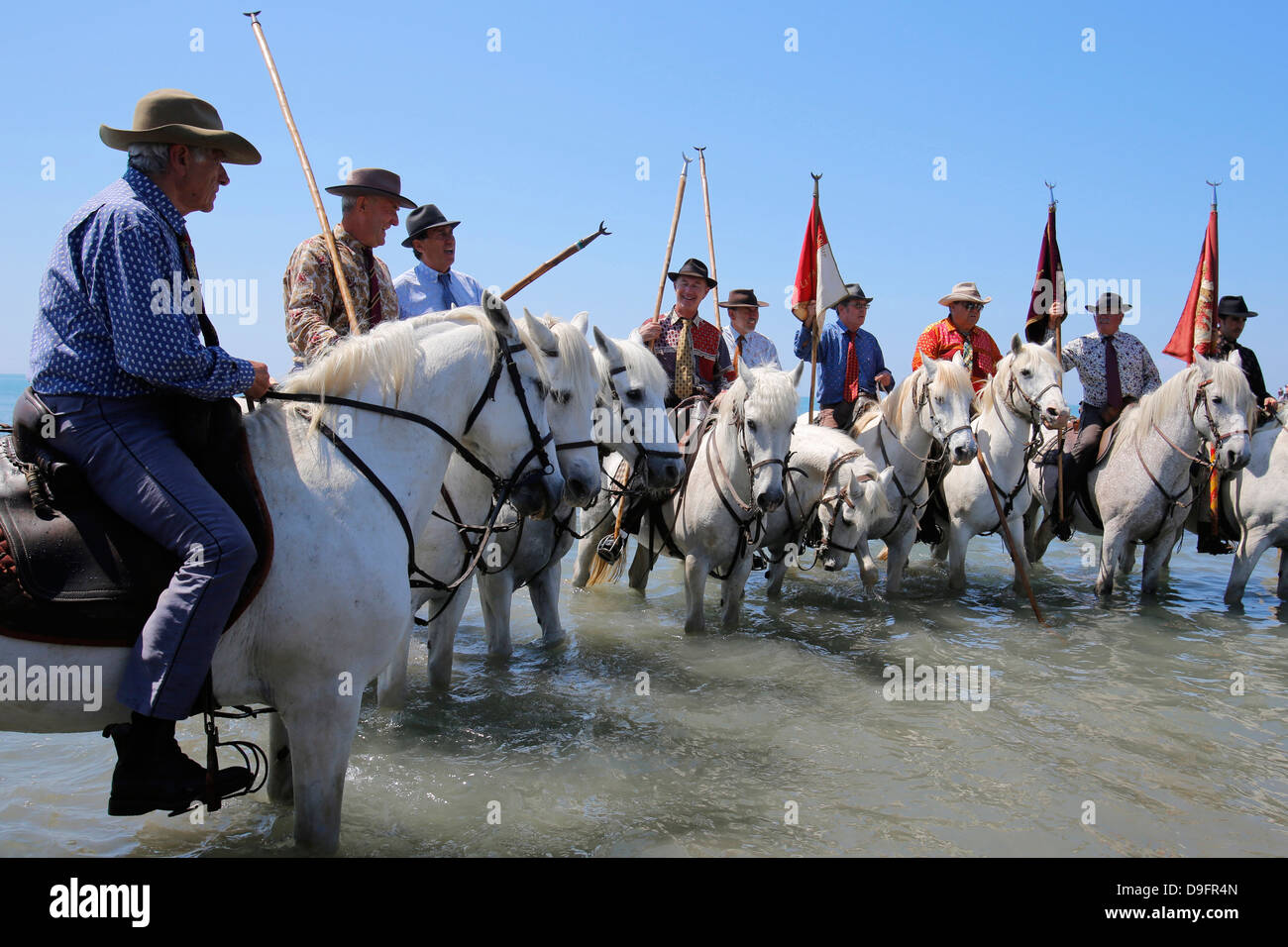 Guardians on horseback escorting the procession to the sea, pilgrimage at Les Saintes-Maries-de-la-Mer, Bouches - Stock Image