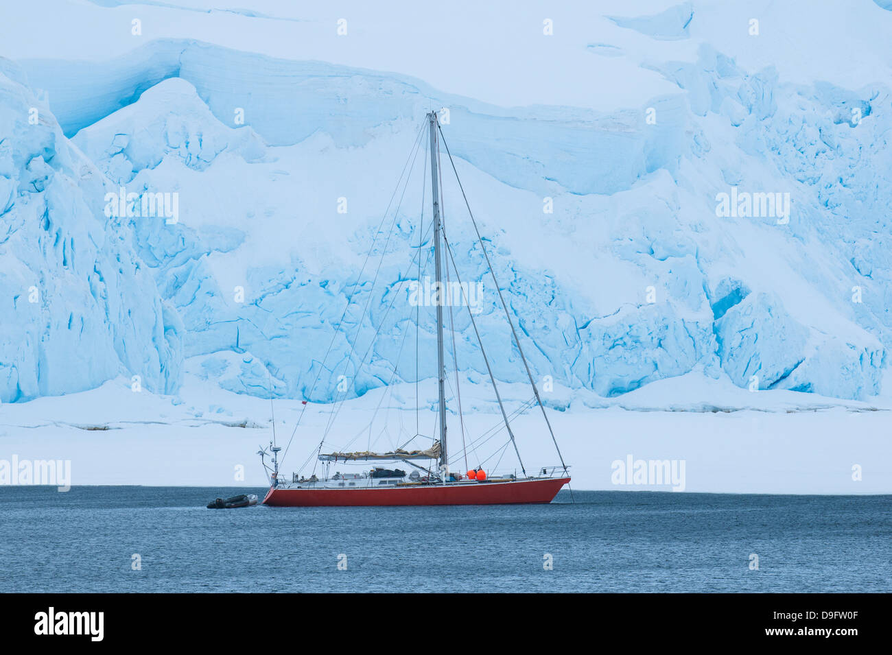 Sailing boat below a huge icefield near Port Lockroy research station, Antarctica, Polar Regions - Stock Image
