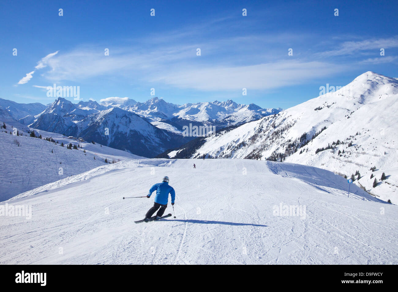 Skiers on Levasset blue piste in winter sunshine, Champagny, La Plagne, French Alps, France - Stock Image
