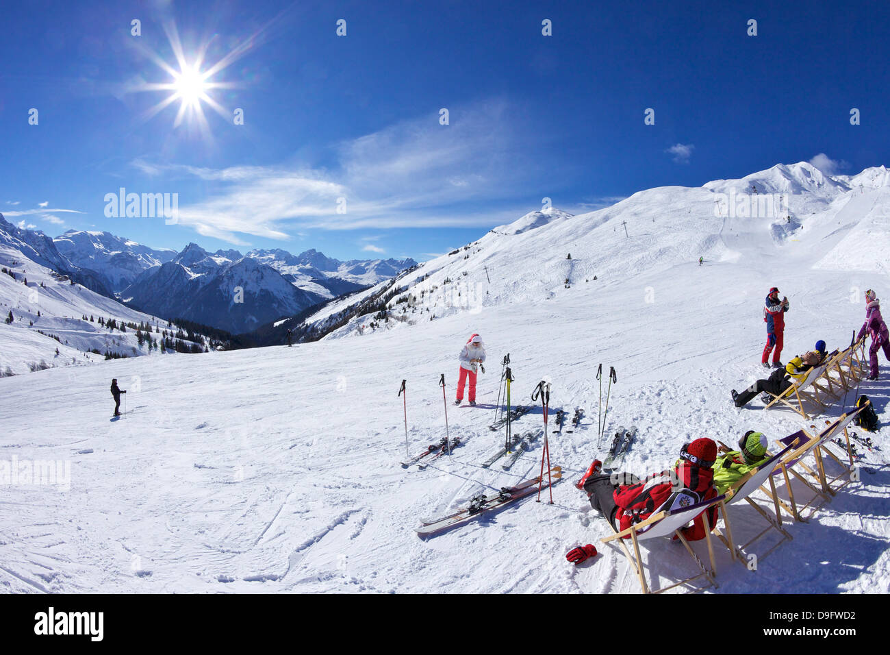 Skiers relaxing at cafe in winter sunshine, Verdons Sud, La Plagne, French Alps, France - Stock Image