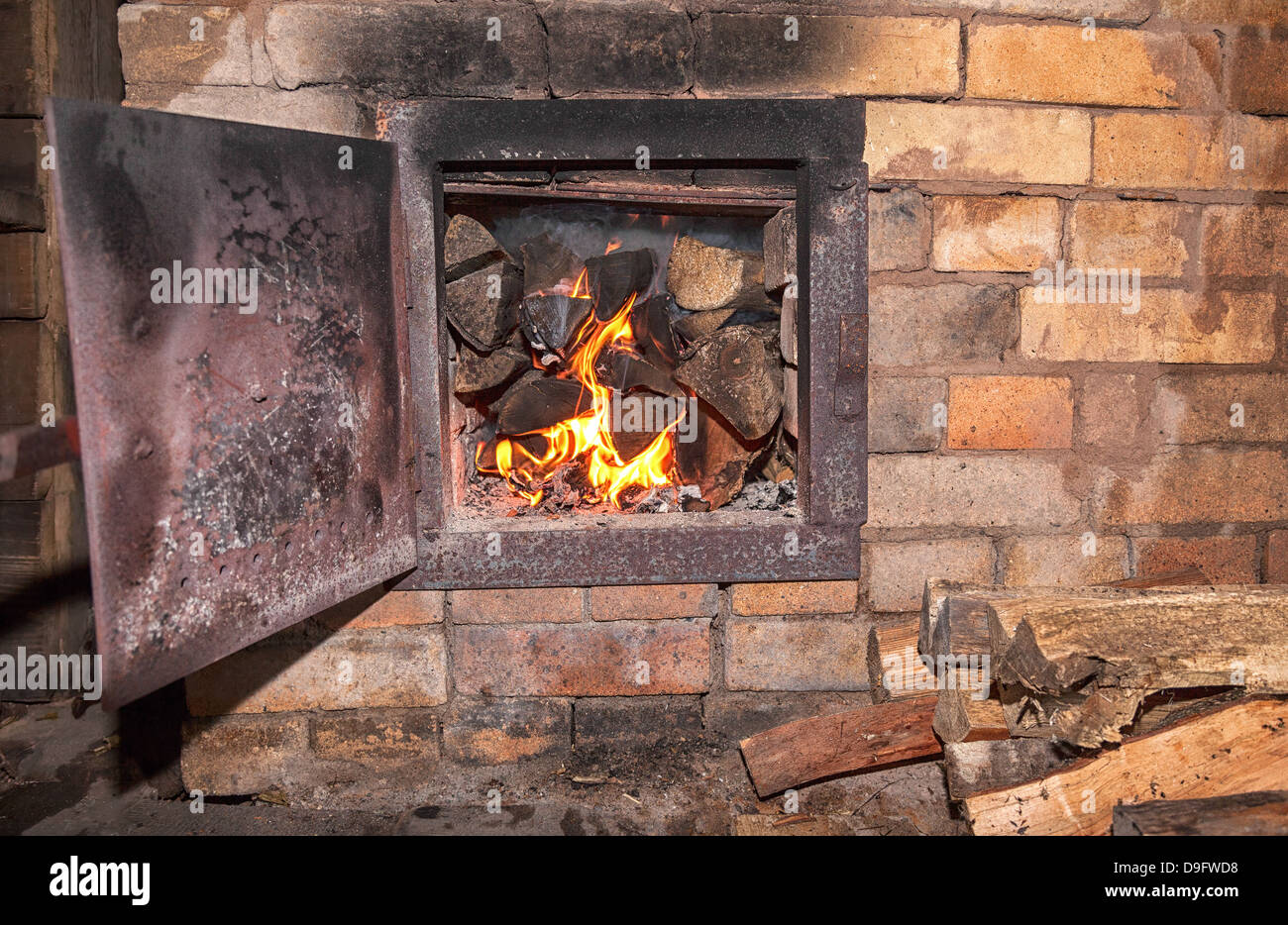 Old stove with open door and burning the wood - Stock Image