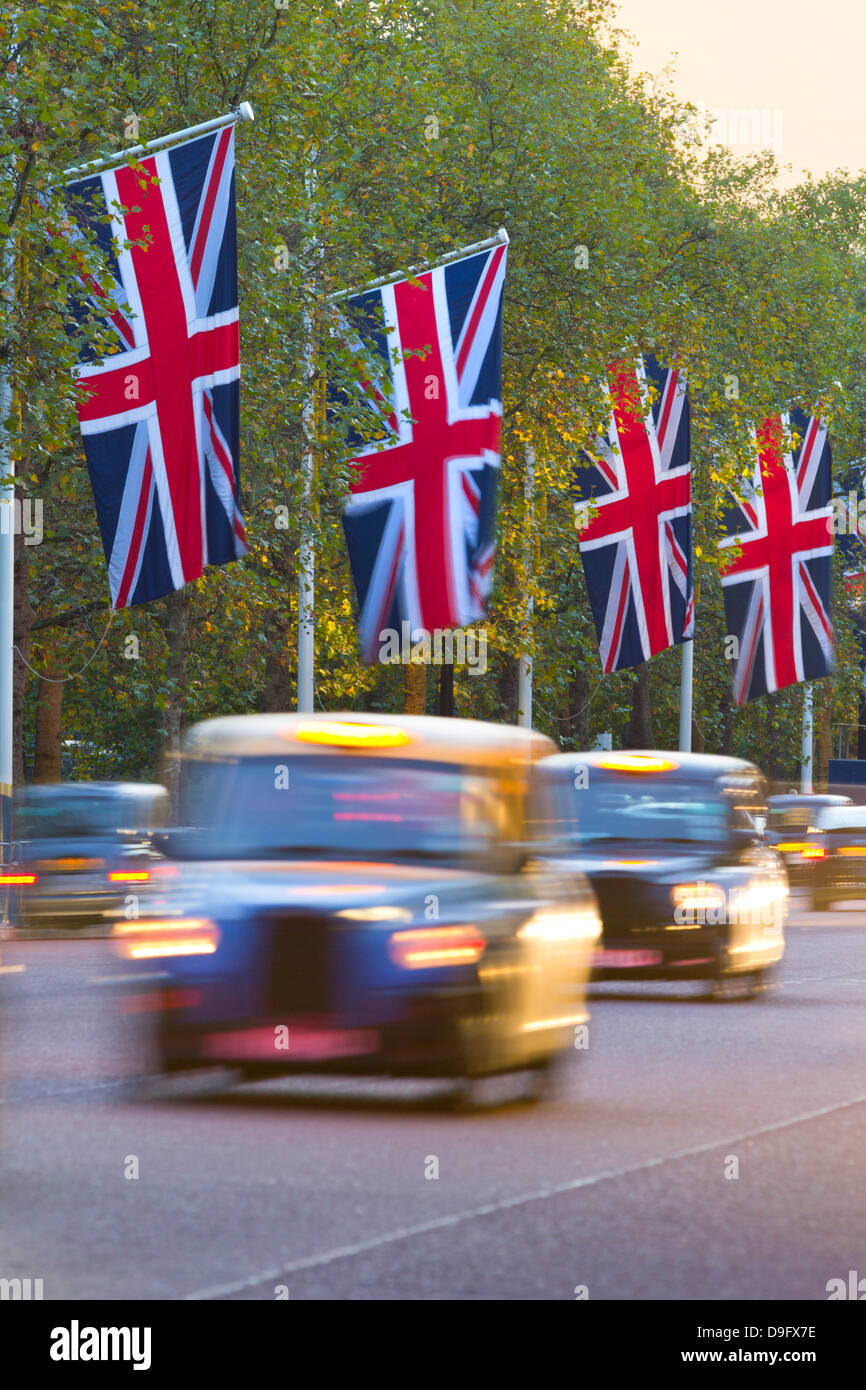 Black cabs along The Mall with Union Jack flags, London, England, UK - Stock Image
