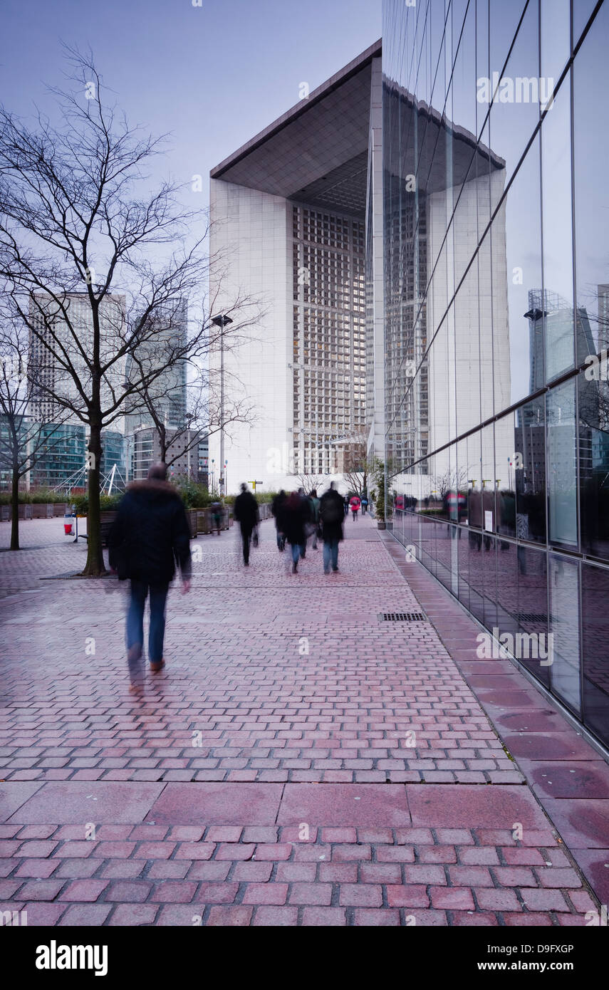 Commuters leaving work in the La Defense area with La Grande Arche in the background, Paris, France Stock Photo
