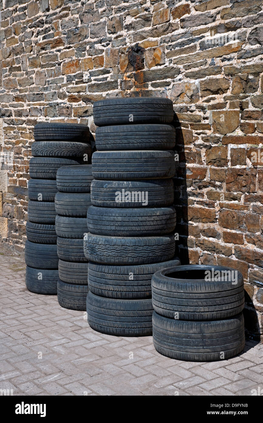 New and used motor vehicle tyres stacked against a garage wall - Stock Image