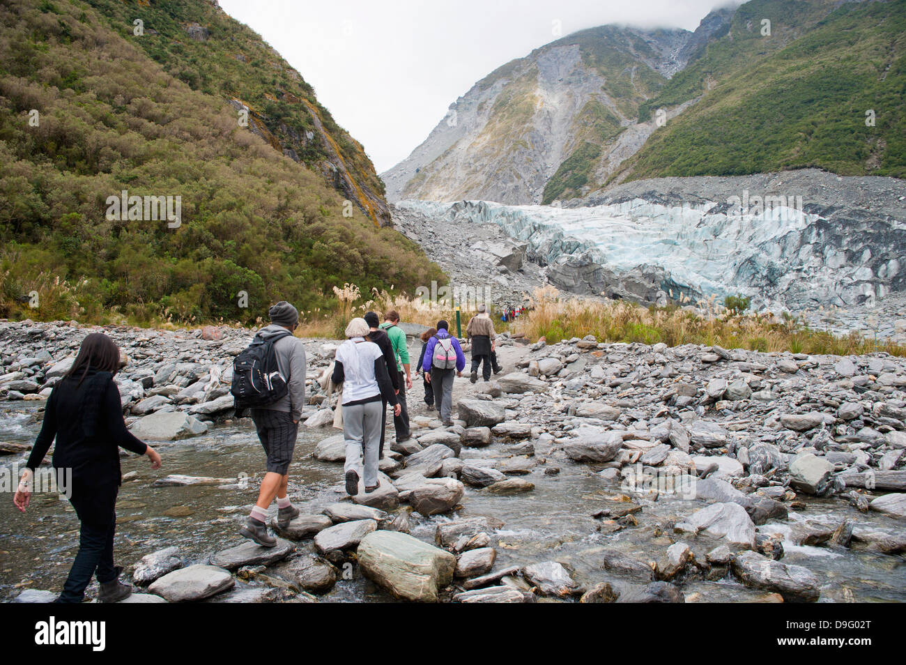 Tourists on Fox Glacier trek, Westland National Park, UNESCO World Heritage Site, South Island, New Zealand - Stock Image