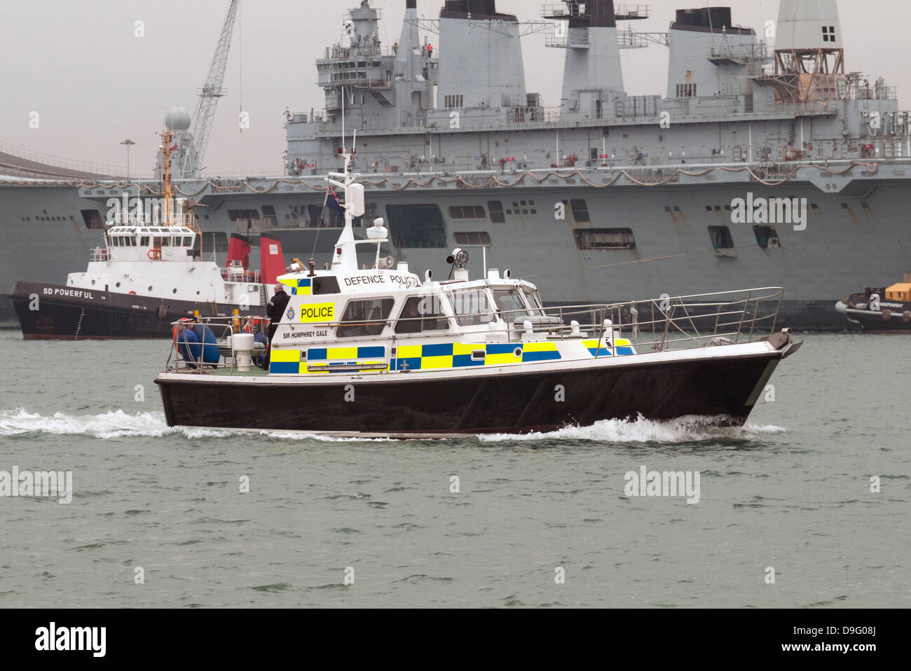 MOD police launch Sir Humphrey Gale on patrol in Portsmouth Harbour with HMS Ark Royal on her final voyage. - Stock Image
