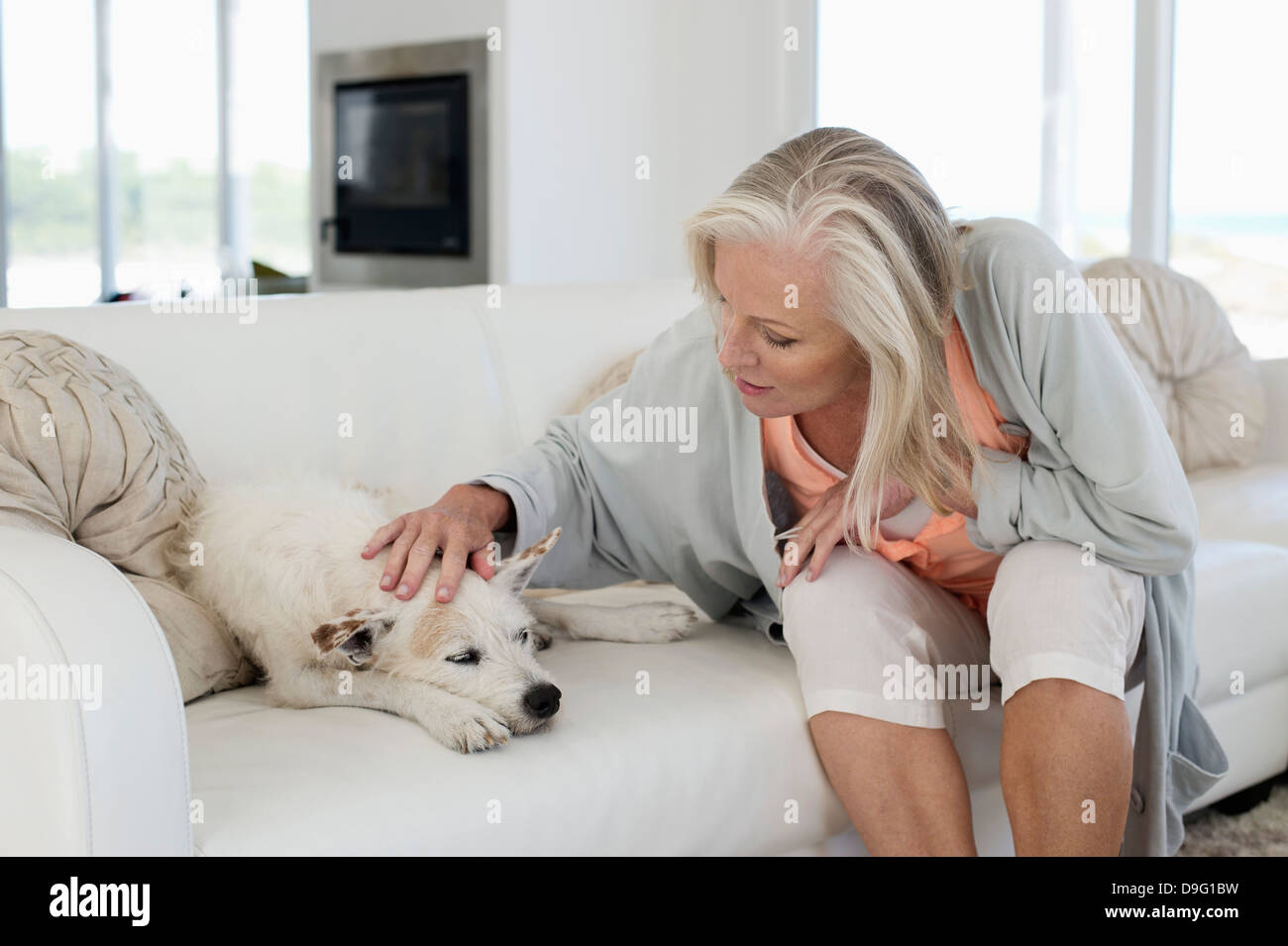 Woman sitting on a couch with her dog - Stock Image