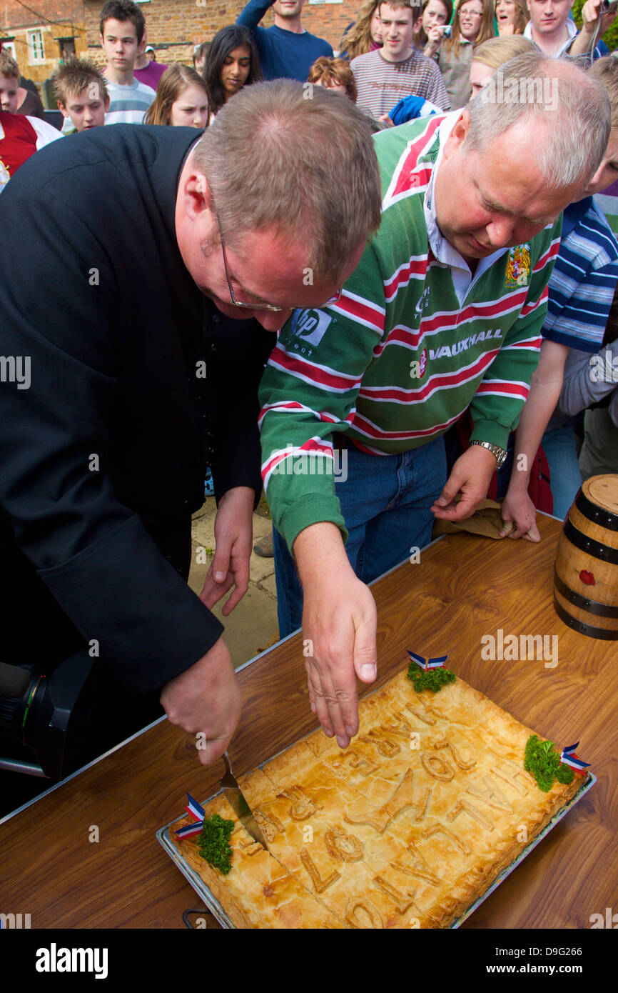 Cutting of the Hare Pie for the Old Annual Custom of Bottle-kicking, Hallaton, Leicestershire, England, UK - Stock Image