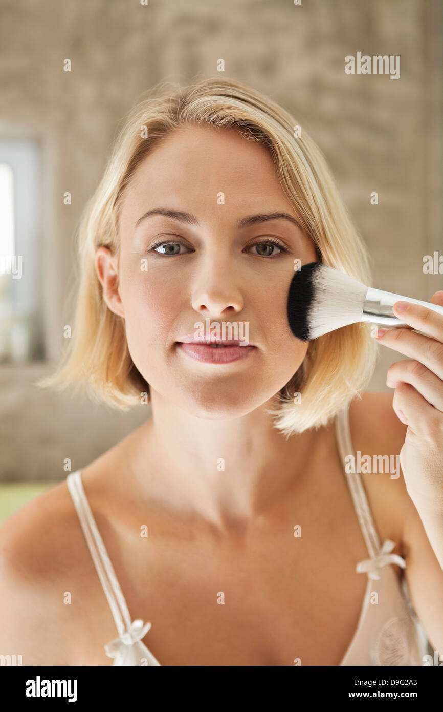 Woman applying make-up with a brush - Stock Image