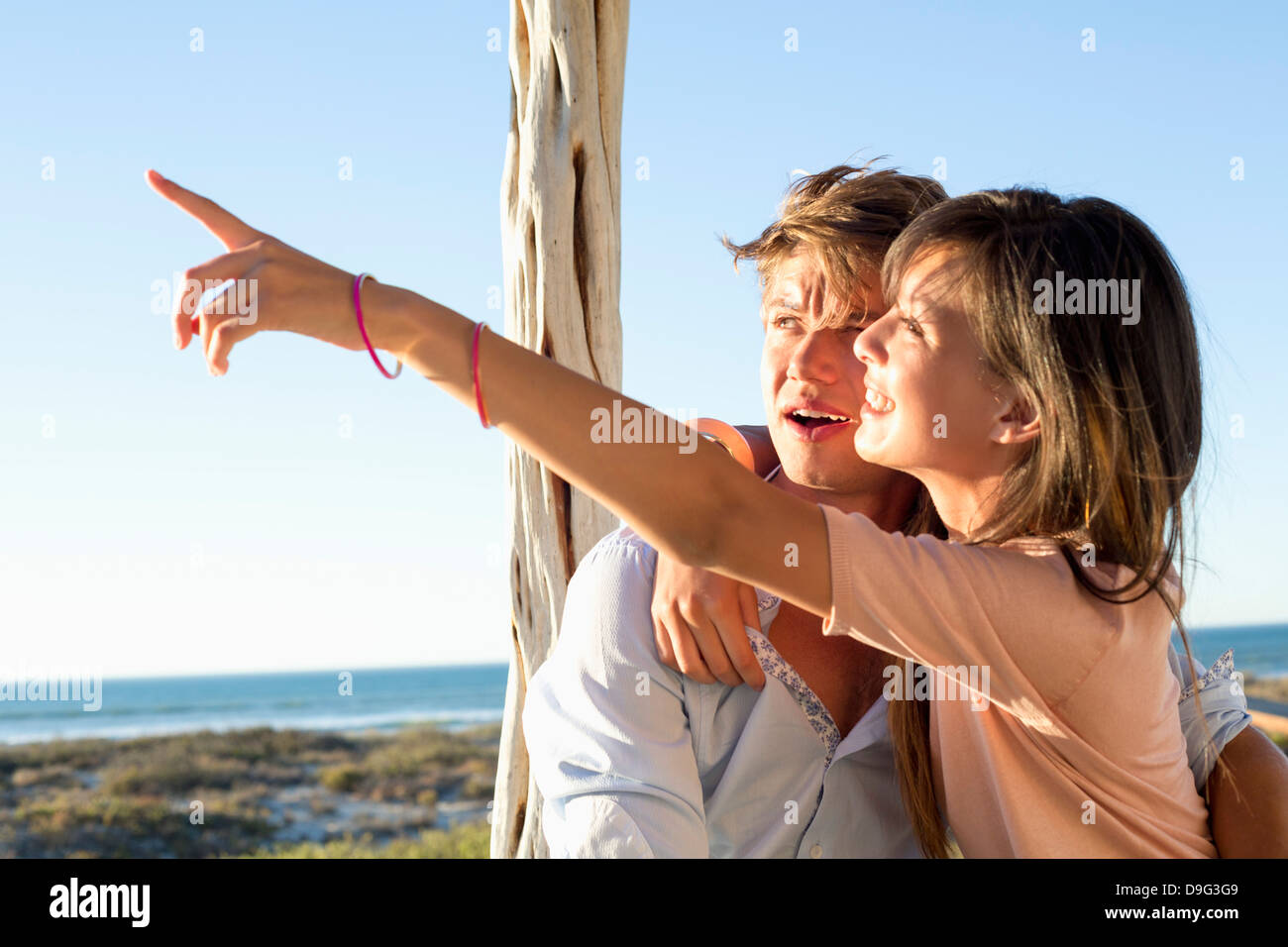 Woman sitting with her boyfriend and pointing away - Stock Image