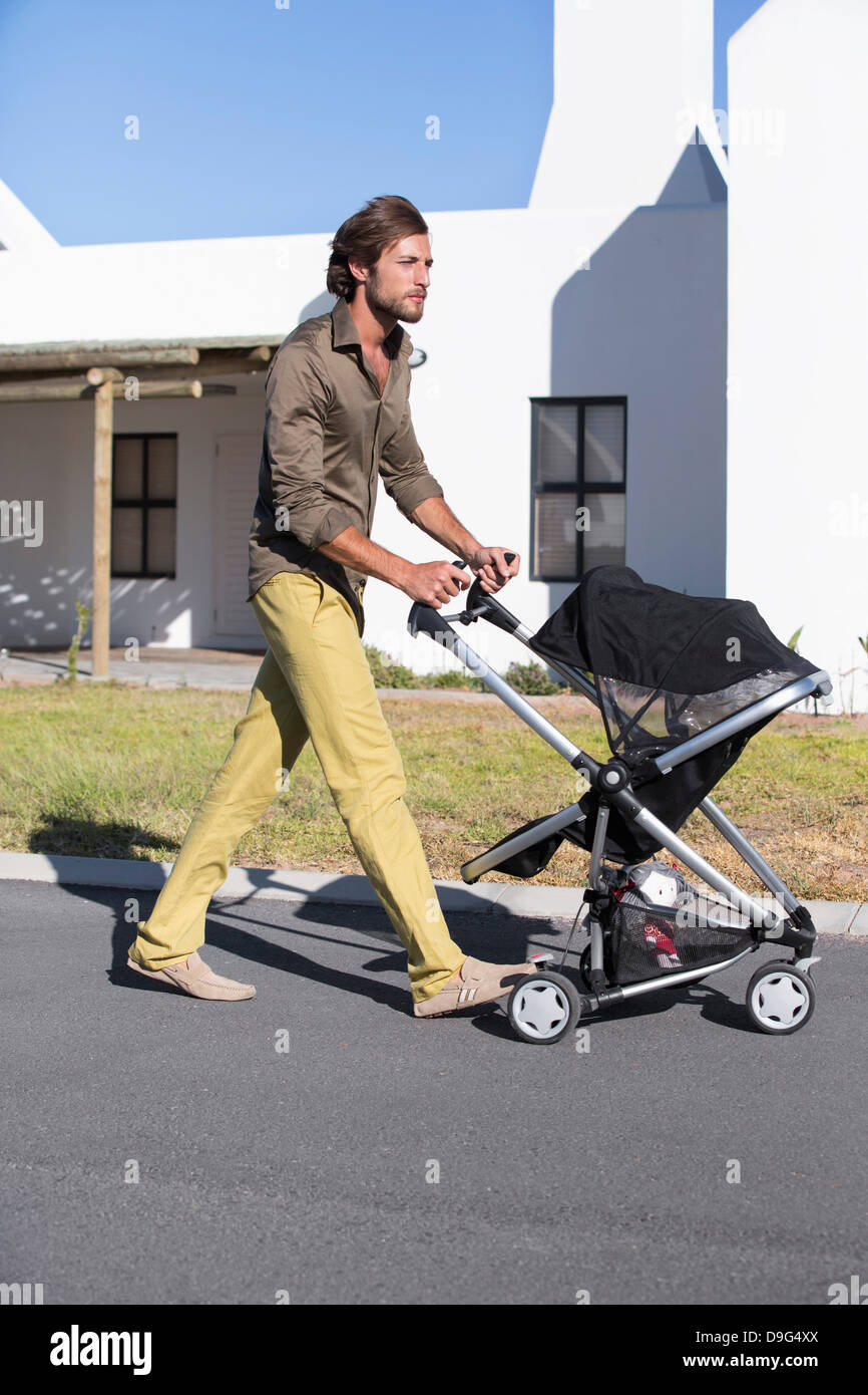 Man pushing a baby stroller on a road - Stock Image