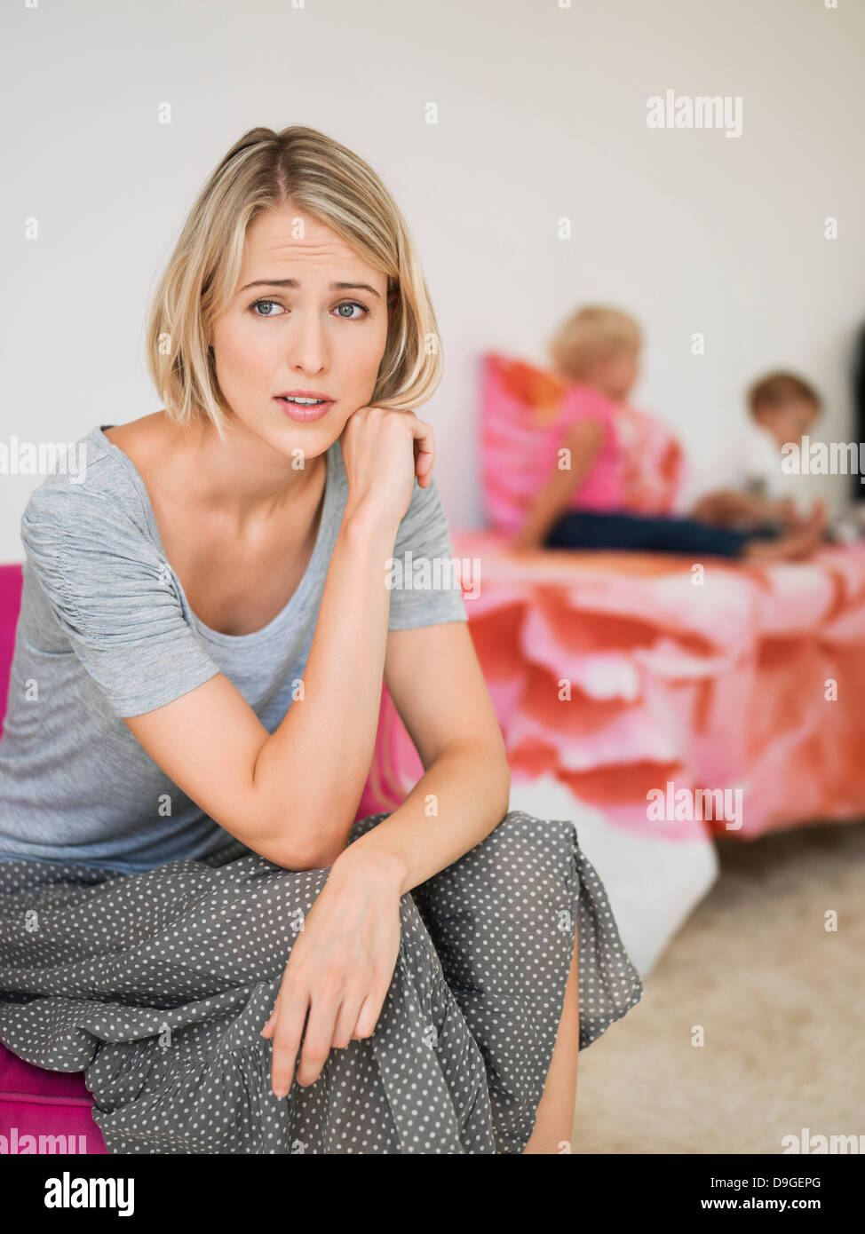 Woman looking worried with her children in the background - Stock Image