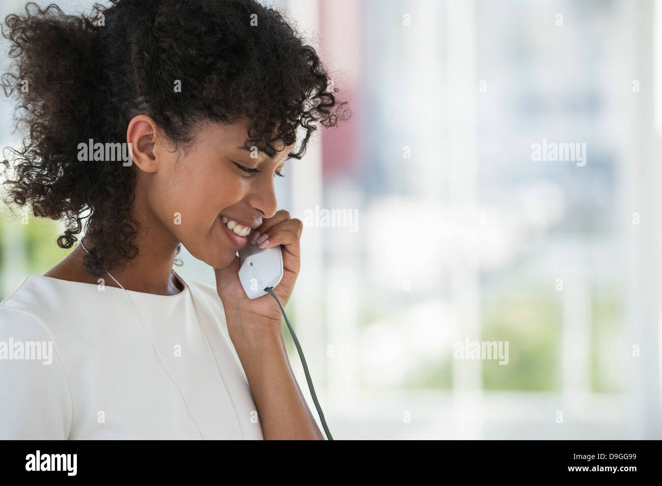 Close-up of a woman talking on a landline phone - Stock Image
