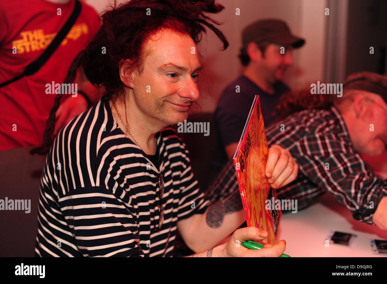 Jeremy Cunningham  signing an album for fans The Levellers recording live performance of the record 'Levelling - Stock Image
