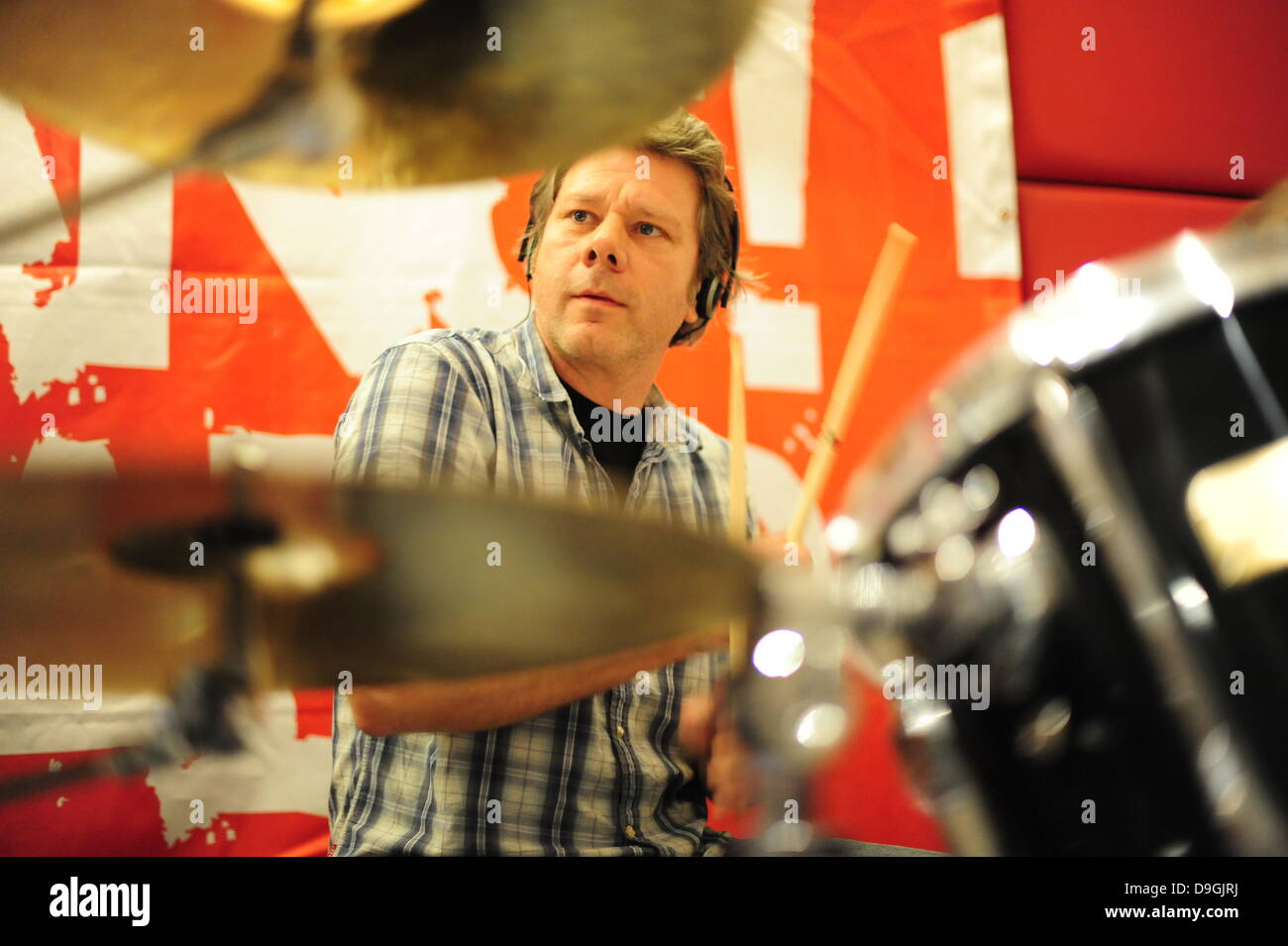 Charlie Heath playing drums for The Levellers The Levellers recording live performance of the record 'Levelling - Stock Image