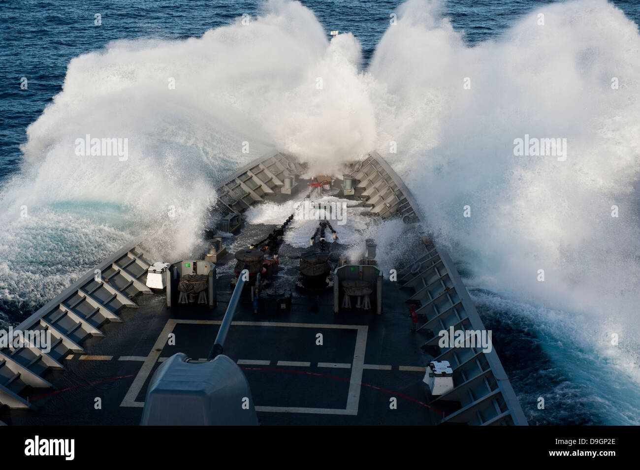 The bow of USS Cowpens plows through a wave in rough seas. - Stock Image