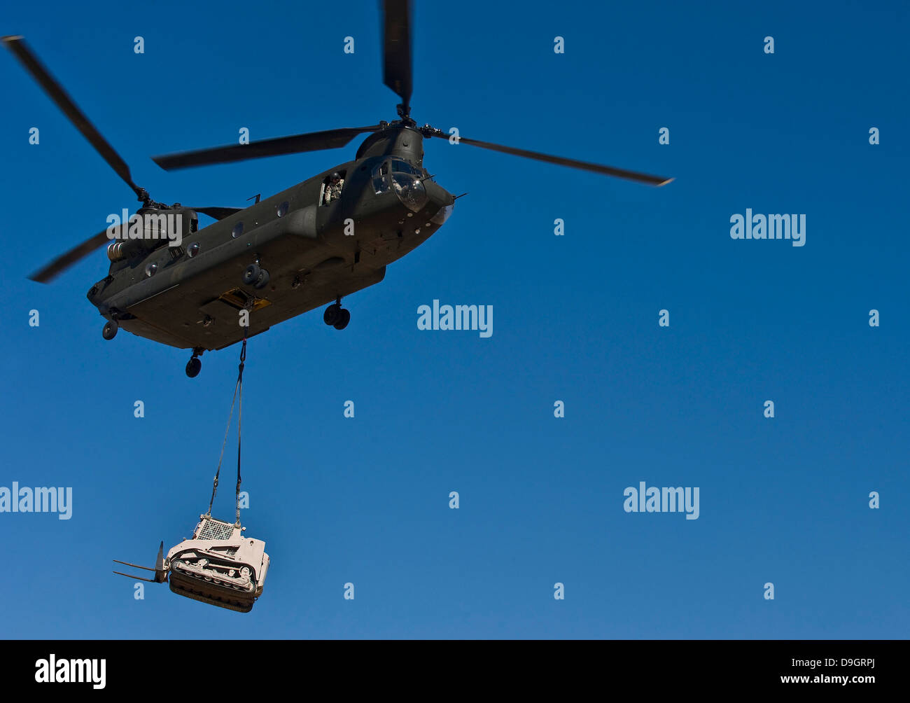 A U.S. Army CH-47 Chinook carries a bulldozer to a drop site. - Stock Image