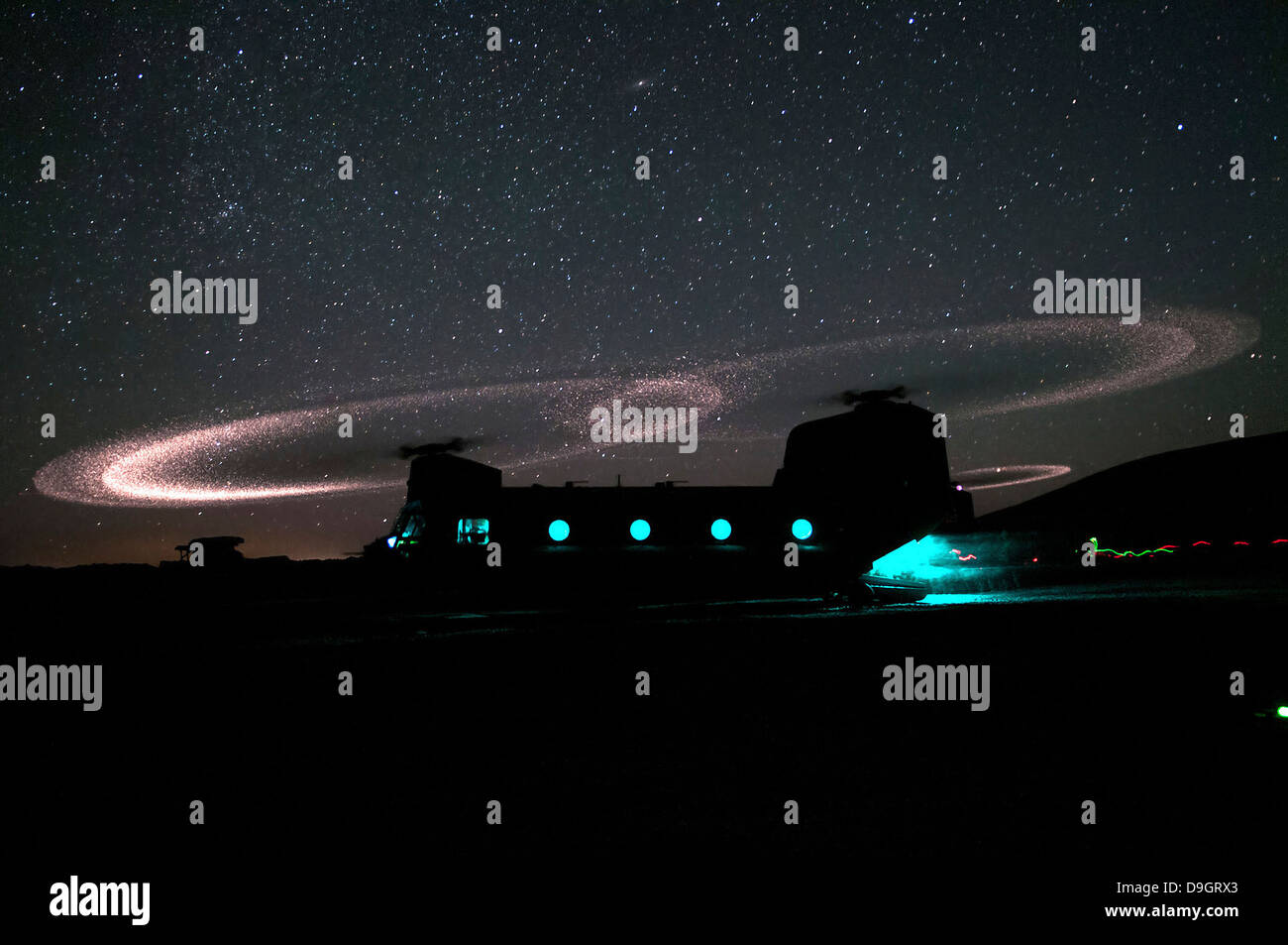 Dust lights up the rotors of a CH-47 Chinook helicopter. - Stock Image